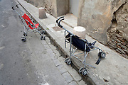 two baby strollers abandoned at the side of the road
