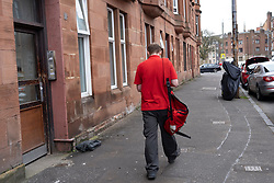 Glasgow, Scotland, UK. 3 April, 2020. Images from the south side of Glasgow at the end of the second week of Coronavirus lockdown. Pictured; Royal Mail postman making deliveries to tenement in Govanhill . Iain Masterton/Alamy Live News
