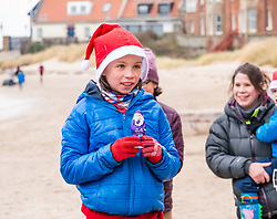 Pictured: Santa Beach Run on the scenic East Lothian coast. This new event is aimed at athletes, casual runners and families. It is hosted by Project Trust with proceeds enabling local school leavers to spend a year volunteering in India/Honduras to teach at a school with few teaching materials. The fastest young girl with her prize. 15 December 2018  <br /> <br /> Sally Anderson | EdinburghElitemedia.co.uk