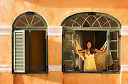 A woman stands at an open window inside of an old fort in St. Croix, US Virgin Islands.