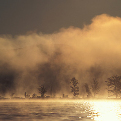 Cranberry Lake, NY.Fog. Trees silhoutted in sunlit mist on Cranberry Lake in NY's Adirondack Park.