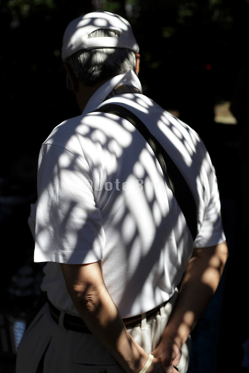 senior man with sunlight pattern from grid above