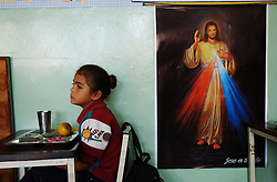 """Scarleth Pérez waits to say grace before eating lunchin her first grade classroom at the Florencio Jimenez school.  The school is one of the new """"Bolivarian"""" Schools which are part of President Chavez's Education Reform.  The new Bolivarian Schools keep students for an entire day, as opposed to a half day, feed the students lunch and offer programs like drama, art and music. While President Chavez touts his programs that benefit the poor, many point to a rising poverty rate and shrinking economy and claim the programs fail to substantially help."""