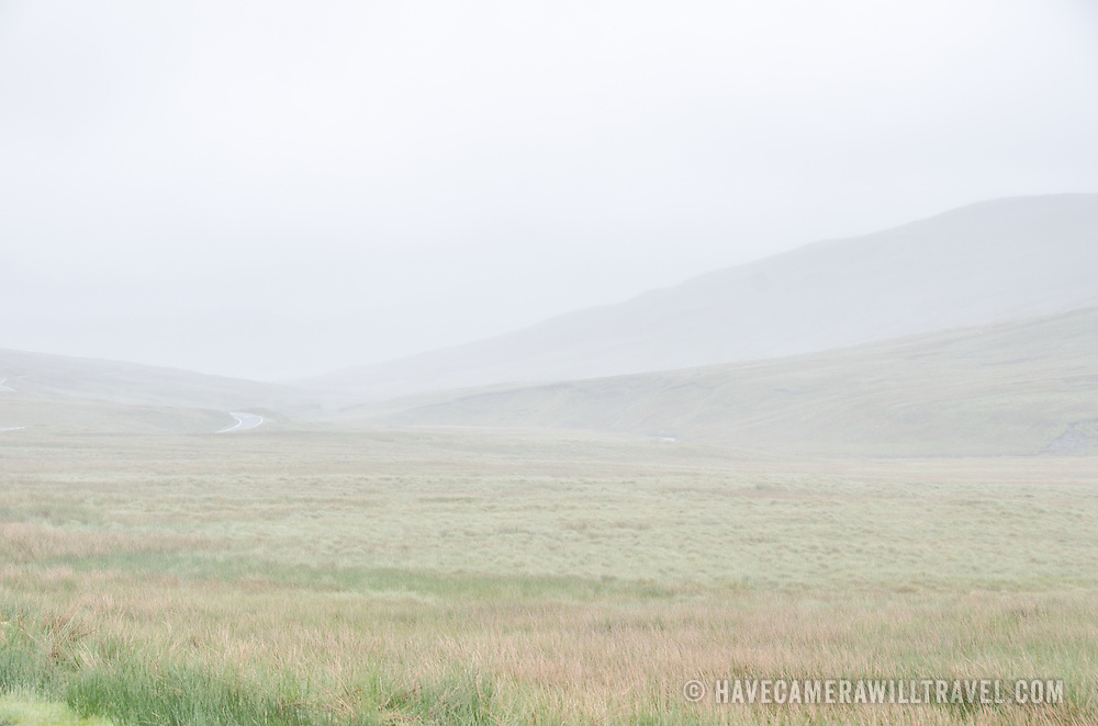 Mist and clouds cover the landscape on a plateau in Snowdonia, Wales.