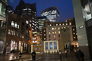 Architecture and commuters during rush hour in the City of London at night, England, United Kingdom.