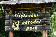 """Triglavski narodni park (TNP) sign, Slovenia. Tolmin gorges (Tolminska korita) are among the longest and deepest gorges in Slovenia and are the lowest point (180 meters elevation) in Triglav National Park (TNP). Walk a trail to the confluence of two gorges (Tolminka and Zadlascica rivers), then along Zadlascica river canyon (locally called Skakalce, """"the jumps"""") up to a chock stone called the """"Bear's Head"""" (Medvedova glava). Walk onwards to the scenic Devil's Bridge (Hudicev most, built 1907), which carries Tolmin-Cadrg road sixty meters above Tolminka River, then walk the loop back to the parking lot at the Triglavski narodni park (TNP) sign, near Zatolmin, Slovenia, Europe. (The Slovene letters sc in Zadla??ica may not display in some media.)"""