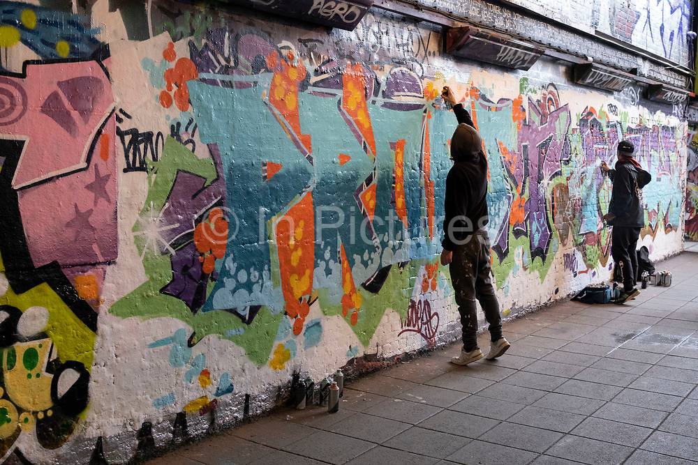 Graffiti artists work on their creations in spray paint street art and graffiti at the popular Leake Street Arches on 5th March 2021 in London, England, United Kingdom. Leake Street is a road tunnel in Lambeth, where graffiti is tolerated and encouraged regardless of the fact that it is against the law. The street is about 300 metres long, runs off York Road and under the platforms and tracks of Waterloo station.