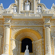 Statues and decorations on the distinctive  and ornate yellow and white exterior of the Iglesia y Convento de Nuestra Senora de la Merced in downtown Antigua, Guatemala.