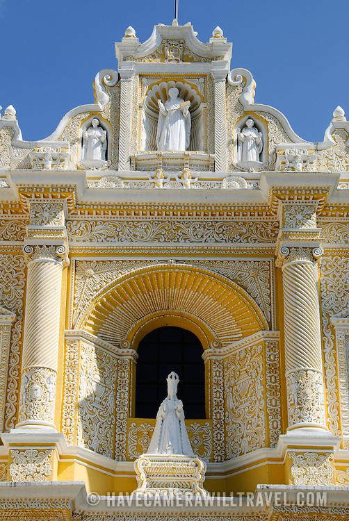Statues and decorations on the distinctive  and ornate yellow and white exterior of the Iglesia y Convento de Nuestra Senora de la Merced in downtown Antigua, Guatemala.