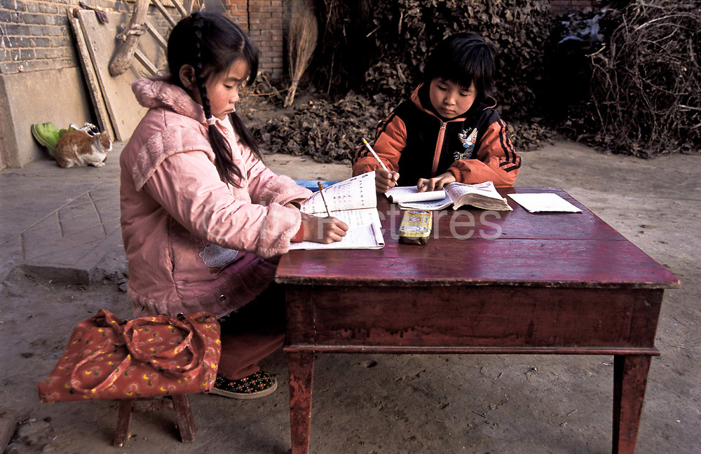 Chen Xiao Sa, 8 years old does her home work with a friend outside her home whilst good daylight allows, Dong Da Jian village, Shaanxi Province.