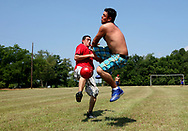 After a week of picking peaches in the sweltering sun, Miguel Arias and Carlos Oso, both of Nayarit, Mexico play soccer on a Sunday afternoon.