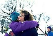 Friends age 45 hugging at end of Lake Phalen cross country ski race.  St Paul  Minnesota USA