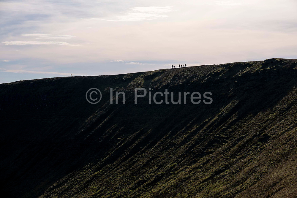 Silhouette of people walking across the mountain ridge between the twined peaks of Pen Y Fan and Corn Du in Brecon Beacons National Park, Wales, Powys, United Kingdom.  Pen Y Fan is the highest point in the Brecon Beacons hill and mountain range in South Wales. The National Park was established in 1957 due to the spectacular landscape which is rich in natural beauty and is run by the National Trust.