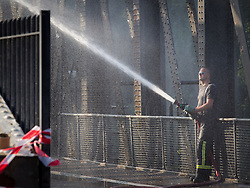 © Licensed to London News Pictures . 09/07/2013 . Manchester , UK . A fireman douses the bridge's frame in the heat . The Barton Road Swing Bridge which links Redclyffe Road and Barton Road over the Manchester Ship Canal , was stuck open today after heat caused the metal frame to expand whilst it was opened to allow a boat to pass beneath . A fire crew doused the metal structure with water to cool it down until it contracted sufficiently to allow the bridge to swing closed . Rush hour traffic backed up for several miles around the Trafford Centre and M60 as a consequence of the road's one-and-a-half hour closure . Photo credit : Joel Goodman/LNP video available here.. http://www.youtube.com/watch?v=ySGwDNzhH8o