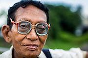 15 JUNE 2013 - YANGON, MYANMAR:  A retired teacher walking along Sule Pagoda Road in Yangon.   PHOTO BY JACK KURTZ
