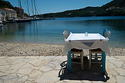 Restaurant table set up for dinner in the sea front in Kioni, Ithaca, Greece. Ithaca, Ithaki or Ithaka is a Greek island located in the Ionian Sea to the west of continental Greece. Ithacas main island has an area of 96 square kilometres. It is the second-smallest of seven main Ionian Islands.