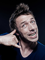 studio portrait on black background of a funny expressive caucasian man phone hand sign