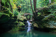 A Small Stone Foot Bridge And Waterfall Running Through The Lush And Green Scenic Gorge Called Old Man's Cave In The Hocking Hills Region Of Central Ohio, USA