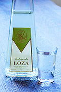 Triangular pyramid shaped Bottle of Loza rakija grappa type grape spirit, a glass of digestif alcohol. In the restaurant and wine bar at the winery. Podrum Vinoteka Sivric winery, Citluk, near Mostar. Federation Bosne i Hercegovine. Bosnia Herzegovina, Europe.