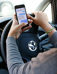 Embargoed to 0001 Friday April 12 POSED BY MODEL File photo dated 13/08/14 of a woman texting on her phone whilst driving. Police have unveiled a new device which can detect when motorists are using their mobile phones while driving.