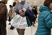male person carrying various paper bags in shopping mall Yokohama Japan
