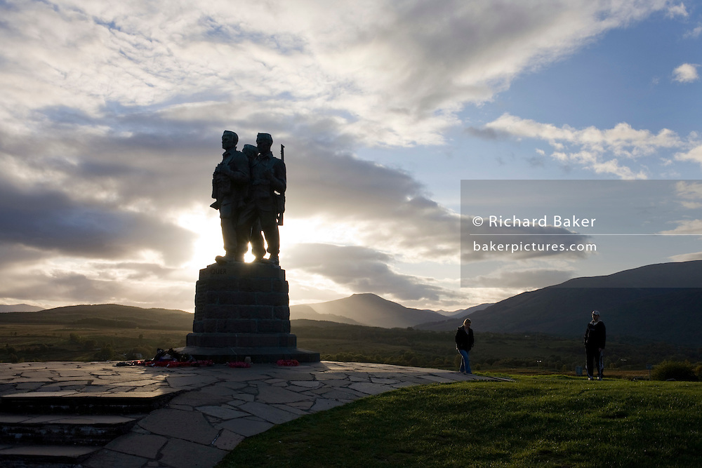 Two visitors pay their respects at the second world war bronze Commando Memorial at Spean Bridge, Scotland