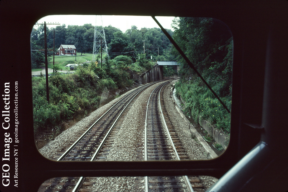 View through window from a locomotive cab on the Union Railroad as it transports steel ingots between industrial plants in the Monongahela Valley. The plants belong to USX, formerly U.S. Steel. Railroad freight hopper cars line up at a coke plant that is part of the bleak rust belt industry landscape.