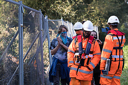 An HS2 security guard (c) is filmed by an anti-HS2 activist after he pocketed an item belonging to a fellow activist during tree felling works alongside HOAC lake in connection with the HS2 high-speed rail link on 21 September 2020 in Harefield, United Kingdom. Anti-HS2 activists continue to try to prevent or delay works for the controversial £106bn HS2 high-speed rail link on environmental and cost grounds from a series of protection camps based along the route of the line between London and Birmingham.