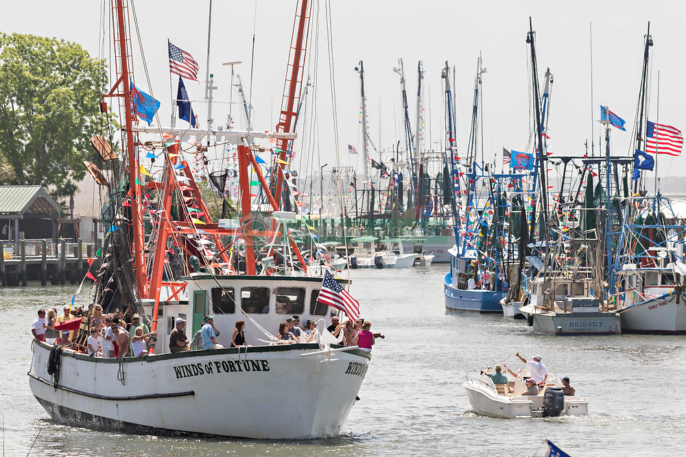 April 30, 2017 - Mount Pleasant, South Carolina, U.S. - Decorated shrimp boats parade past the commercial fishing docks down Shem Creek during the annual Blessing of the Fleet signifying the start of the commercial shrimping season in South Carolina. Coastal shrimping is part of the low country heritage but has been declining rapidly with rising costs and increased foreign competition. (Credit Image: © Richard Ellis via ZUMA Wire)