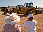 31 JULY 2009 --  BUCKEYE, AZ: Alex Flores (CQ) and his son Erasmo Flores (CQ) 12, from Laredo, TX, look at equipment before bidding at the auction on the former Pylman Dairy Farm in Buckeye. The auction was handled by Overland Stockyards from Hanford, CA. The Arizona dairy industry is struggling to survive the worst milk economy some have ever seen. Due to the global recession, overseas demand for Arizona dairy products has plummeted, forcing prices down while production costs have stayed stable or gone up. For every $1 dairymen earn from milk sales, it cost them $1.50 to produce the milk. Photo by Jack Kurtz