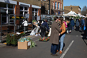 Couple kiss at Columbia Road flower market on Mothers Day, and its last open Sunday for a while due to Covid-19 on what would normally be a busy, bustling market day with hoards of people out to buy flowers and socialise, the numbers of people out is a fraction of a regular Sunday on 22nd March 2020 in London, England, United Kingdom. All of the East End Sunday markets have been affected by the Coronavirus outbreak, with some completely closed and some currently partially open. Coronavirus or Covid-19 is a new respiratory illness that has not previously been seen in humans. While much or Europe has been placed into lockdown, the UK government has announced more stringent rules as part of their long term strategy, and in particular social distancing.