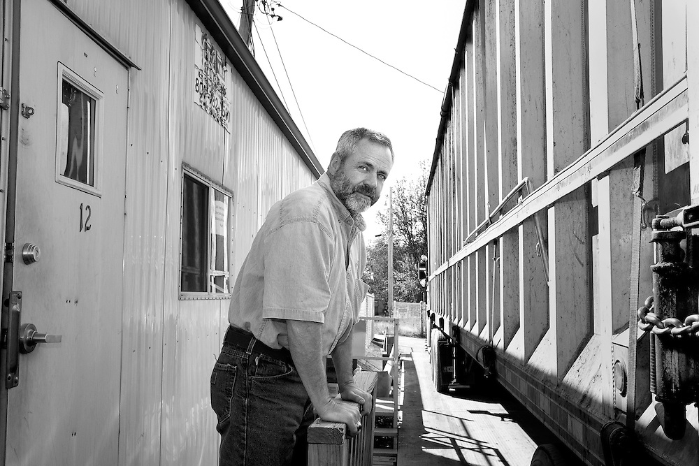 B&W photo of male employee outside weigh house in between house and waste transfer truck