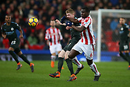 Kurt Zouma of Stoke City ® challenges Kevin De Bruyne of Manchester City. Premier league match, Stoke City v Manchester City at the Bet365 Stadium in Stoke on Trent, Staffs on Monday 12th March 2018.<br /> pic by Andrew Orchard, Andrew Orchard sports photography.