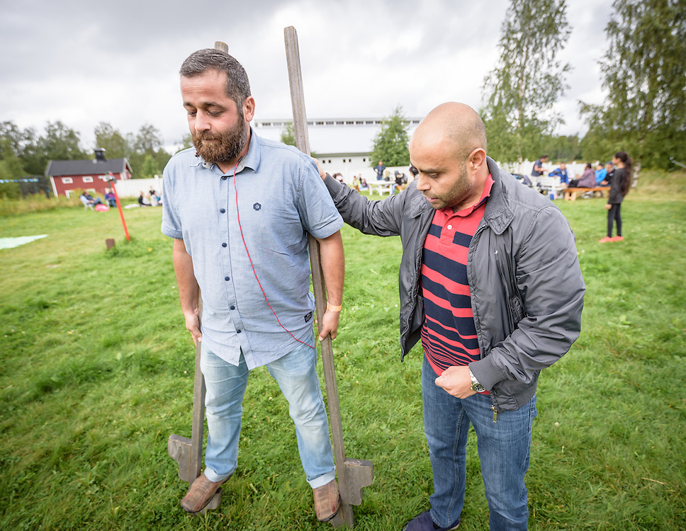 """13 August 2016, Norrbyskär, Umeå, Sweden: Adnan Al Mousa, a Syrian refugee recently arrived in Sweden, practices walking on stilts, helped on by Muhammad Al Hamid from Syria, during the Kul-Tur Fest (""""Culture Festival""""). The event, which attracted hundreds of people, set out to offer a meeting place for Swedish culture and new forms of cultural expression, and featured baking competitions, dance workshops, book discussions, fingernail painting and music, among other things."""