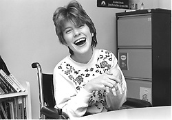 Young woman with physical impairment who is wheelchair user; laughing,