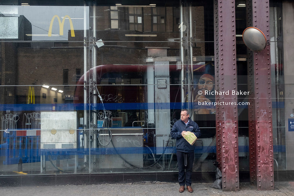 A Londoner holds a bag containing a takeway snack outside Waterloo Station where a small McDonalds is located, on 11th March 2021, in London, England.