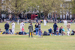 Licensed to London News Pictures. 01/05/2021. London, UK. Families relax and enjoy the Bank Holiday weekend while watching the cricket on a pack Richmond Green in South West London today. This month Covid-19 restrictions were lifted with more freedoms to meet friends and have picnics in the parks as pubs and staycations open up for the long May Bank Holiday weekend with temperatures expected to reach 14c in the South East with a possibility of rain forecast. Photo credit: Alex Lentati/LNP