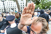 A man who says he didn't want his children to be photographed puts a hand in front of our photographer's lens meanwhile students were shouting and holding banners and placards outside Downing Street, Whitehall in central London on Sunday, Aug 16, 2020. Students are reacting to the downgrading of A-Level results as a result of the Covid-19 pandemic. <br /> Thousands of pupils across England have expressed their disappointment at having their results downgraded after exams were cancelled due to coronavirus. A-levels results that were announced on 13 August. Some 40 per cent of students across England have received downgraded results. (VXP Photo/ Vudi Xhymshiti)