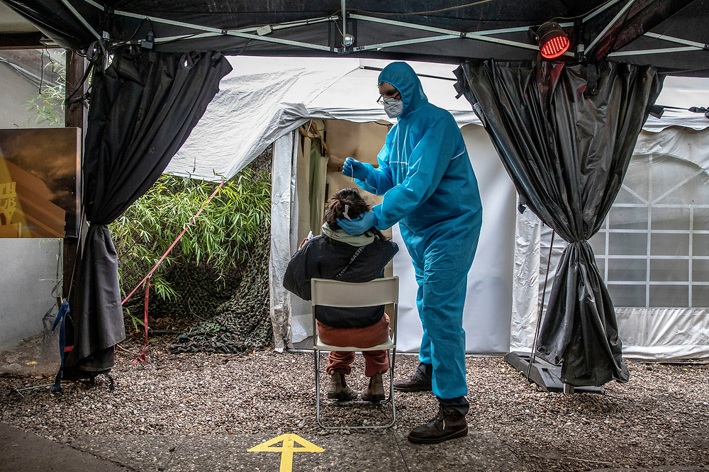 Medical personnel staff member performs a covid antigen rapid swab tests on a person at a covid-19 test station outside the Kitkat night club in Berlin, Germany, December 13, 2020. Berlin's world famous KitKatClub has initiated a fast covid-19 tests operation in its premises People are able to set an online appointment and arrive to have a covid antigen rapid test swab test in what was reported by local media outlet as the lowest price in the German capital. The club itself is closed since early 2020 due to the health restrictions imposed on cultural venues in Germany.