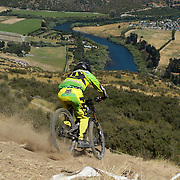 Reuben Olorenshaw from Nelson in action during the New Zealand South Island Downhill Cup Mountain Bike series held on The Remarkables face with a stunning backdrop of the Wakatipu Basin. 150 riders took part in the two day event. Queenstown, Otago, New Zealand. 9th January 2012. Photo Tim Clayton