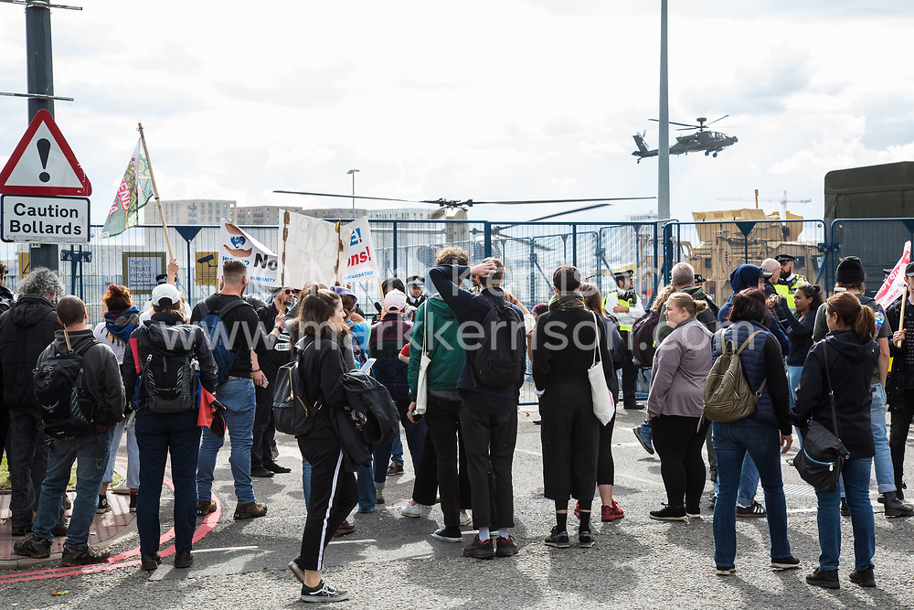 London, UK. 7 September, 2019. Activists observe military helicopters landing outside ExCel London during the sixth day of Stop The Arms Fair protests against DSEI, the world's largest arms fair. The sixth day of protests was billed as a Festival of Resistance and included performances, entertainment for children and workshops as well as activities intended to disrupt deliveries to ExCel London for the arms fair.
