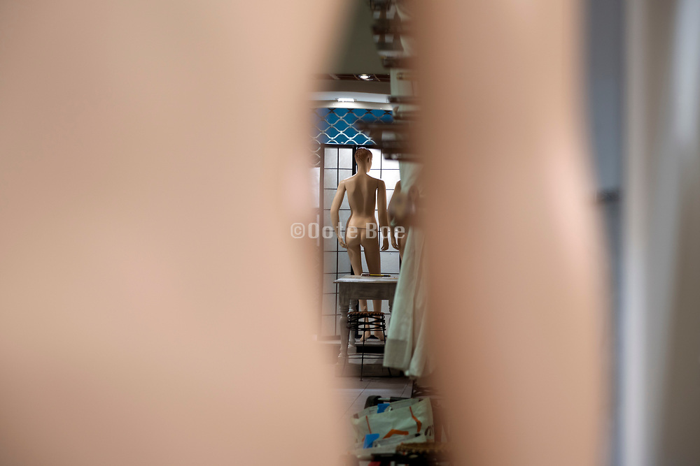 undressed mannequin in a clothing store window display behind a screen