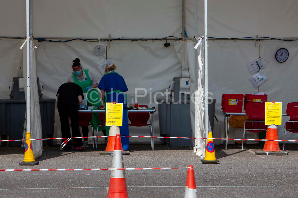 NHS staff prepare to see a patient who remains in their car at a drive-through Primary Care Clinical Assessment Centre where potentially infectious and symptomatic Coronavirus patients can be assessed and treated by a doctor or a nurse, in a safe site, on the 16th of April 2020 in Dover, United Kingdom. This is not a COVID-19 testing facility, all patients will only be clinically assessed on site as there is no community testing currently available. All patients have been referred to this centre by NHS 111 or their GP.