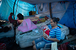 As Christmas approaches, Diana Galeano cuddles her baby Estefanie, 8 days old, inside a makeshift shelter that they share with other families on the side of the highway in La Lima.<br /> <br /> Like Diana, thousands are forced to live on the side of the road. The humidity as the floods go down has brought millions of midges and mosquitos, there is no sanitation, food is scarce, and this is how they will be living well into the new year.<br /> <br /> Outside, a neighbour has built a Nativity scene from things he found in the mud.