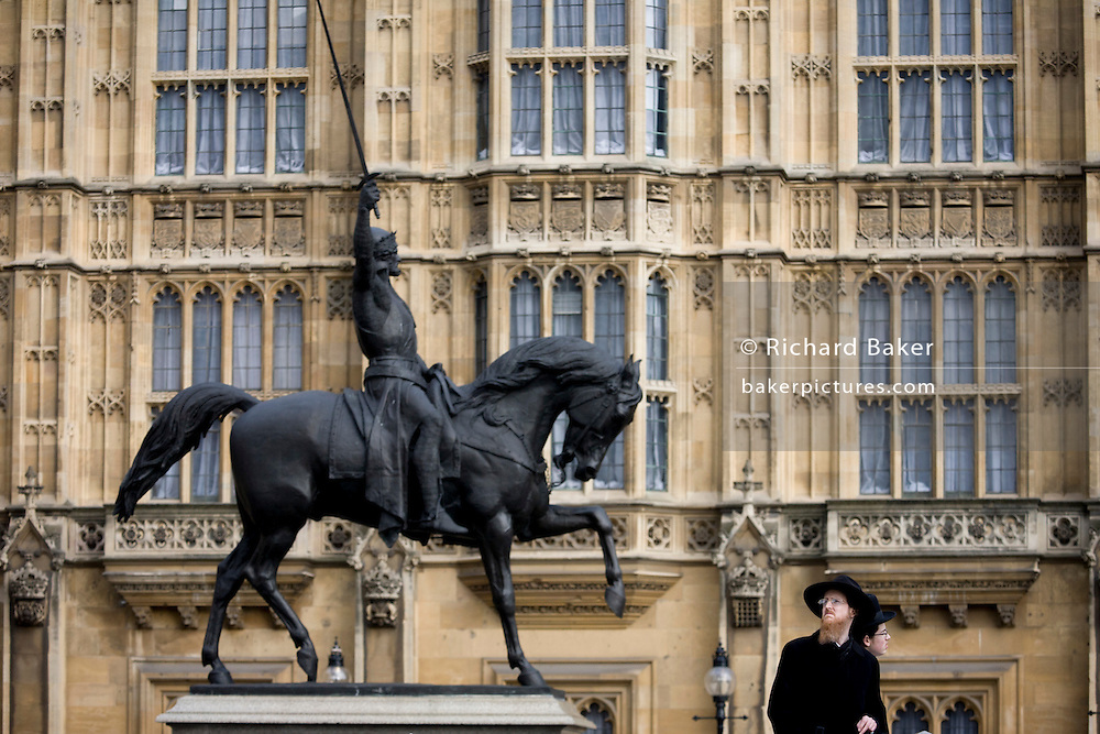 Orthodox Jewish men with the statue of King Richard 1st while visiting the exterior of Britain's parliament in Westminster, London. Richard Coeur de Lion is a Grade II listed equestrian statue of the 12th-century English monarch Richard I, also known as Richard the Lionheart, who reigned from 1189–99. It stands on a granite pedestal in Old Palace Yard outside the Palace of Westminster, facing south towards the entrance to the House of Lords. It was created by Baron Carlo Marochetti,
