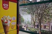 Wall's ice cream ad on telephone kiosk and regeneration project hoarding image at Elephant & Castle, London borough of Southwark.