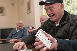 An OAP playing dominos' in a Day Centre