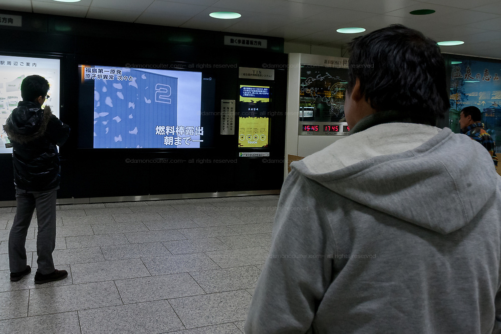 People watching news about the nuclear reactor fire on a tV screen in Shinjuku Station after a magnitude 9 earthquake and large tsunami hit the Tohoku region of north east Japan  on March 11th killing nearly 20,000 people and causing massive destruction along the whole coast, and a melt-down at the Fukushima Daichi nuclear power station. Tokyo, Japan. march 15th 2011