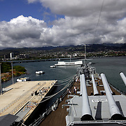 Pearl Harbor, HI, July 18, 2007: The Pearl Harbor Memorial site marks the spot where Japan attacked the U.S. Pacific fleet on December 7, 1941 and drew America into WWII.  The USS Missouri with it's large guns protruding stands near the USS Arizona memorial. The treaty to end the war was signed aboard the USS Missouri.(Photograph by Todd Bigelow/Aurora)