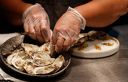Kitchen staff  preparing Oysters with Garlic, Parmesan and Guanciale (pork jown bacon). Atico, Fort Worth, Texas, USA. Atico is a Spanish tapas bar atop a Stockyards hotel and is owned by Tim Love.